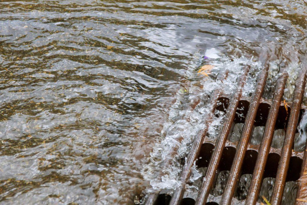 Arbeiter werden durch Abwasserkanal gespült